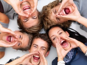 Closeup of happy young friends smiling lying on white floor and